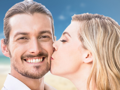 Man smiling while woman kisses his cheek