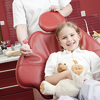 Young girl in dentist chair with lollipop