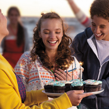 Smiling teen with birthday cupcakes