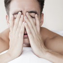 Man in bed with hands covering face